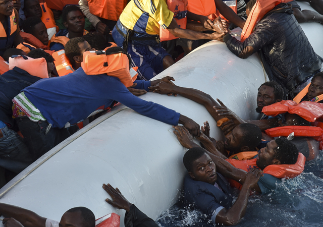 Migrants and refugees panic as they fall in the water during a rescue operation of the Topaz Responder rescue ship run by Maltese NGO Moas and Italian Red Cross, off the Libyan coast in the Mediterranean Sea, on November 3, 2016.