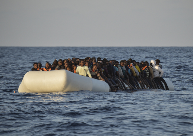 migrants and refugees on a rubber boat before to be rescued by the ship Topaz Responder run by Maltese NGO Moas and Italian Red Cross off the Libyan coast in the Mediterranean Sea, on November 3, 2016
