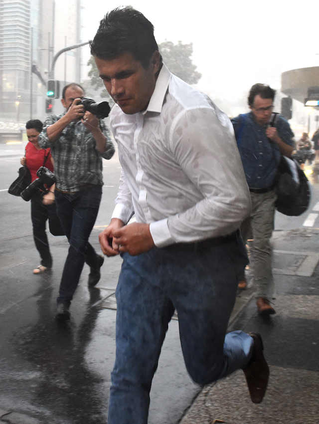 Rain and wind batter Gable Tostee as he runs from the Supreme Court in Brisbane on the day the jury retired to consider a verdict. (AAP Image/Dave Hunt)