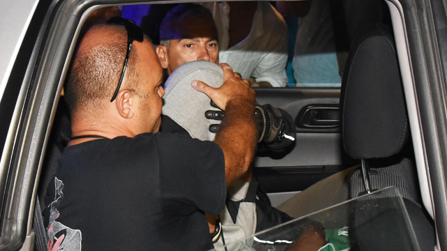 In this photo taken on Saturday, September 2, 2017, a man is escorted by police officers after being arrested in Rimini, Italy. (Associated Press)