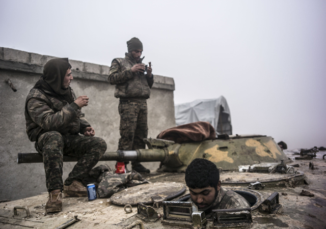Syrian People's Protection Units (YPG) members sit in a tank in frontline of Raqqa, on January 7, 2016. YPG fight against Daesh to liberate the city of Raqqa. (AFP)