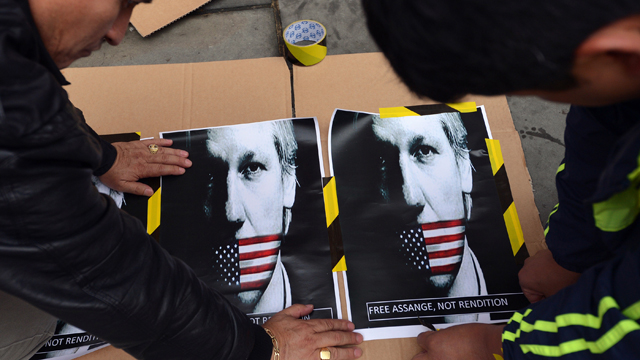 Supporters of WikiLeaks founder Julian Assange prepare a placard with posters showing Assange's portrait with a US flag over his mouth outside the Ecuadorian embassy in central London on June 21, 2012. Source: AFP