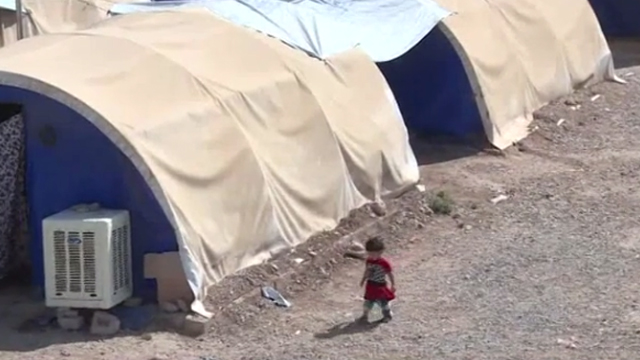 A young girl wanders through the displaced persons camp, with officials telling reporters women and children will likely be extradited to their home nation without charge. (RT)