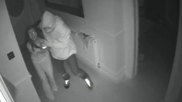 A hooded thug grabs Dr Waheed and leads her upstairs where she is held hostage with her son while thieves ransack her home. Source: Supplied