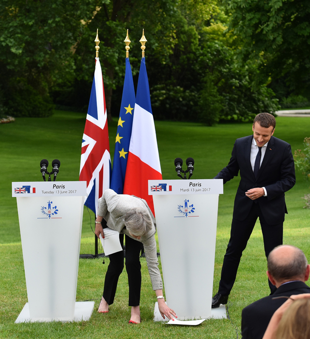 British Prime Minister Theresa May drops her speech notes as she arrives for a joint press conference with French President Emmanuel Macron after their meeting at the Elysee Palace garden in Paris