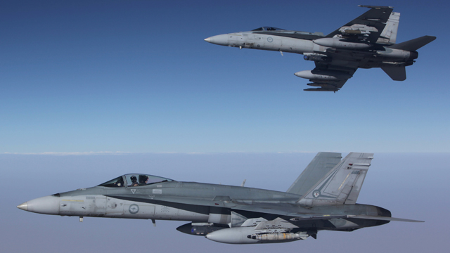 F/A-18A Hornets from Australia's Air Task Group fly in formation with a Royal Australian Air Force KC-30A