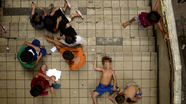 Homeless children play on a staircase at the Light Railway Train Carriedo station in Manila. Photo: AFP