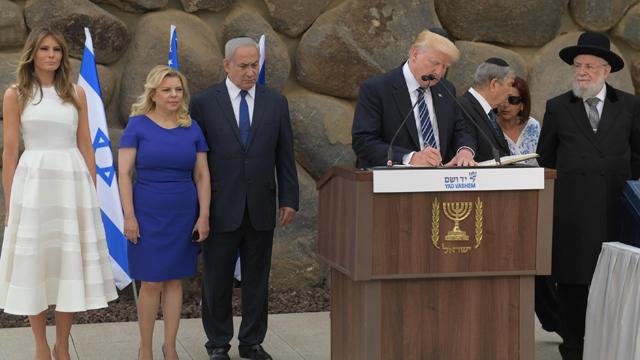 Donald Trump signs the Yad Vashem guest book as wife Melania and Israeli Prime Minister Benjamin Netanyahu watch on. Credit: Israeli Prime Ministry Media Office / Amos Ben Gershom / Anadolu Agency