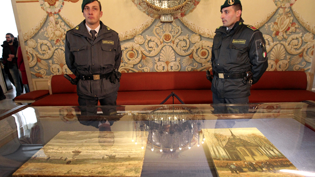"""Two Italian policemen of the Guardia di Finanza (Financial Police) stand guard by the two recently recovered stolen paintings by late Dutch artist Vincent Van Gogh entitled """"Congregation Leaving the Reformed Church in Nuenen"""" and """"The Beach At Scheveningen During A Storm"""""""