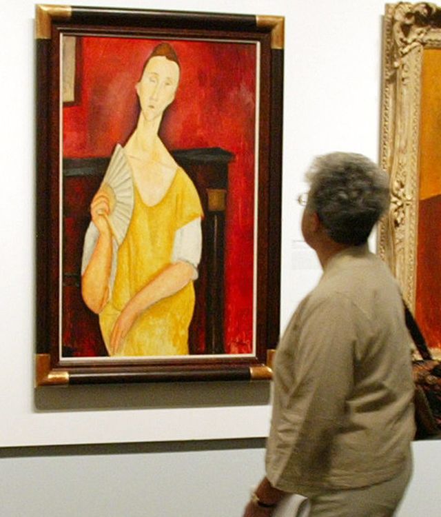 "A visitor looks at ""La Femme à l'éventail"" (Woman with a Fan) by Amedeo Modigliani during an exhibition at The Jewish Museum in New York. Source: AFP"