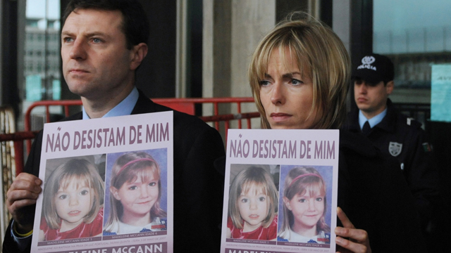 """Gerry (L) and Kate McCann pose with boards portraiting their missing daughter Madeleine reading """"don't give me up"""" as they leave the Tribunal Civil de Lisboa in Lisbon on February 10, 2010,"""