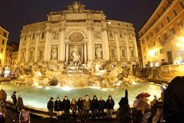 Tourists pose in front of the Trevi fountain in Rome. (Getty)
