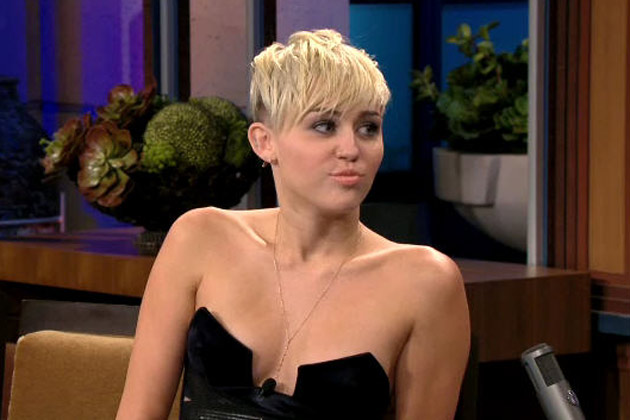 Watch: Miley Cyrus almost pops out of top on Jay Leno, he talks to her chest
