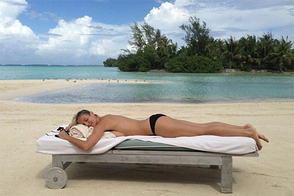 Heidi Klum sunbaking topless on an island
