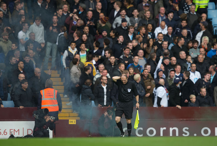 <b>Two men have been arrested after a linesman was hit by a smoke bomb at an English Premier League match.</b><br/><br/>Tottenham Hotspur had just taken the lead against Aston Villa when it's believed one of their fans threw the canister toward the playing surface.<br/><br/>Trailing black smoke, it hit the assistant referee on the neck, causing him to stumble forward and forcing a stoppage in play.<br/><br/>In any form, objects thrown from the stands can be incredibly dangerous, as these videos prove...