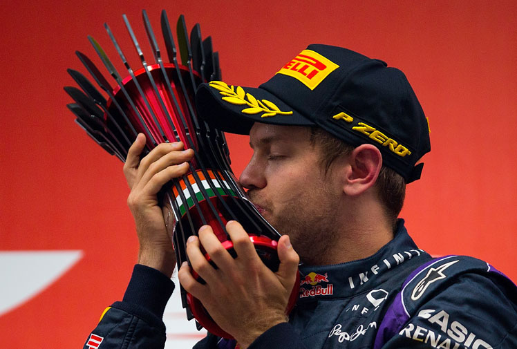 <b>Sebastian Vettel has become Formula One's youngest four-time world champion after winning the Indian Grand Prix. </b><br/><br/>The 26-year-old German has joined Juan Manuel Fangio and Michael Schumacher as the only others to achieve the feat.<br/><br/>Vettel celebrated in spectacular fashion by spinning doughnuts in front of the grandstand. He then stood on top of his Red Bull and saluted the crowd before bowing to his car in mock worship.<br/><br/>(All images Getty)