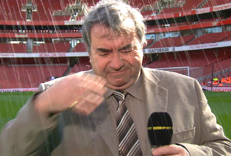<b>It's not always fun and games being a sports reporter, as a British football commentator recently found out.</b><br/><br/>The BBC's Jonathan Pearce was preparing for a pre-match report from Arsenal's Emirates Stadium when he received an unexpected soaking from the pitchside sprinklers.<br/><br/>The unwelcome shower didn't put the veteran commentator off his game, however, and he was able to see the funny side as he delivered his report - albeit with a soaking wet suit.<br/><br/>We've said it before, sports reporting often presents dangers. Just take a look at these videos.<br/>
