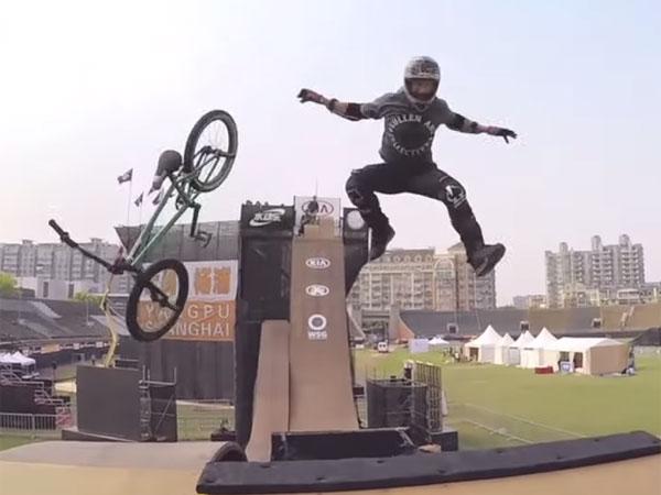 BMX rider switches bike mid-stunt