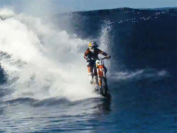 Daredevil Maddison surfs wave on a motorbike