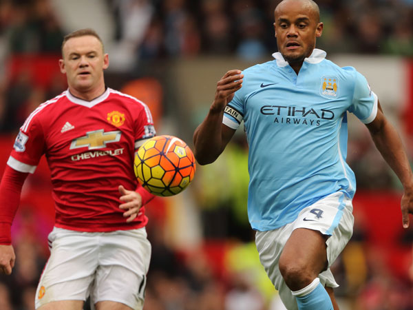 City's Vincent Kompany (R) leads Wayne Rooney to the ball. (Getty)