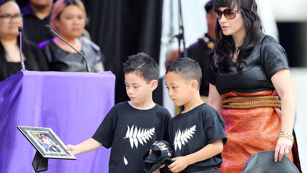 Jonah Lomu's sons place a photo on the casket. (AAP)