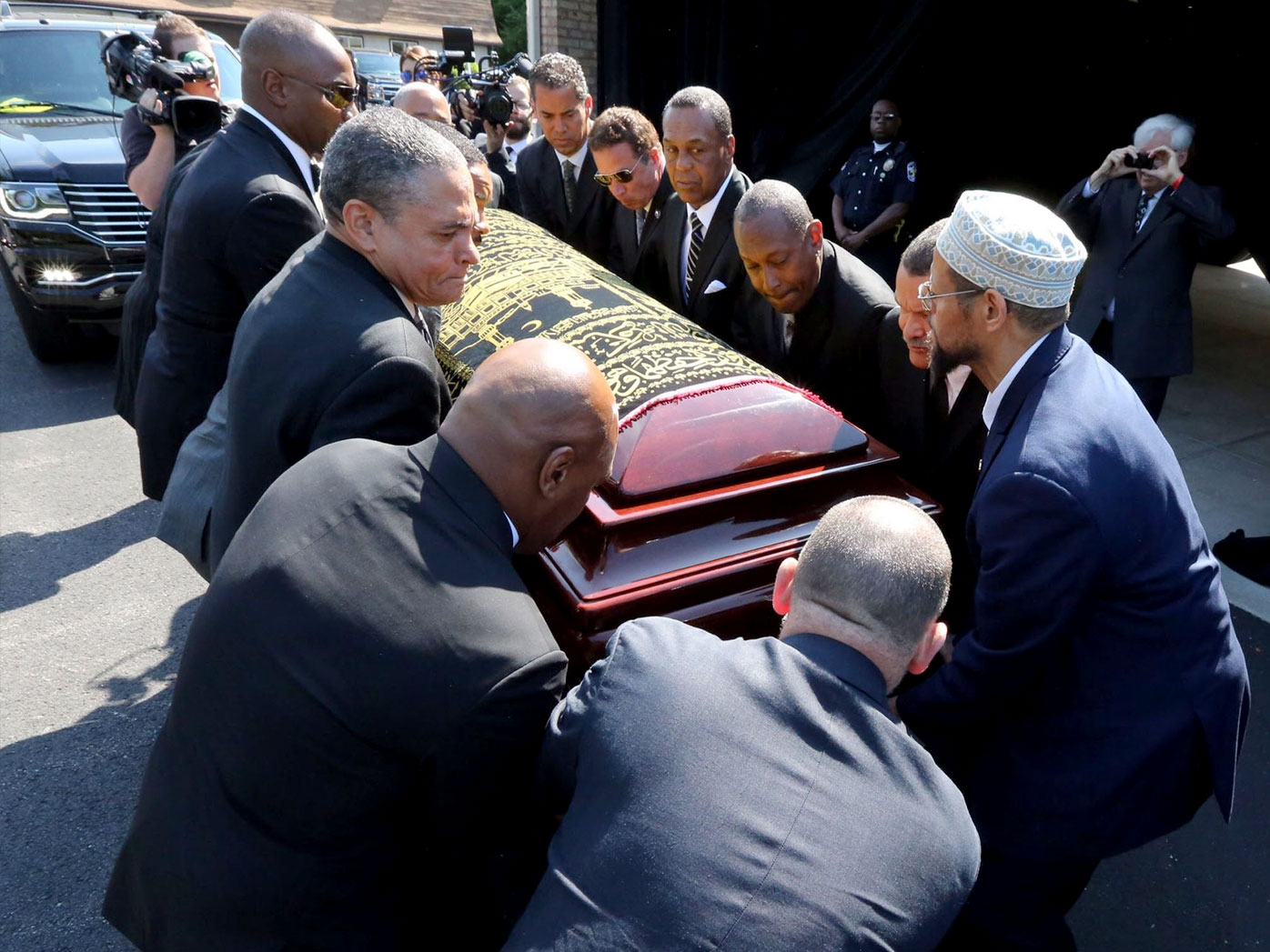 Mike Tyson is among pallbearers lifting Muhammad Ali's coffin into the hearse. (AAP)