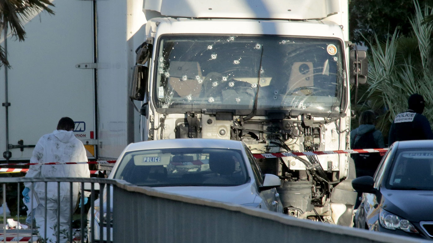 Investigators examine the bullet-riddled truck on the morning after it was used in a terror attack in Nice. (Getty)