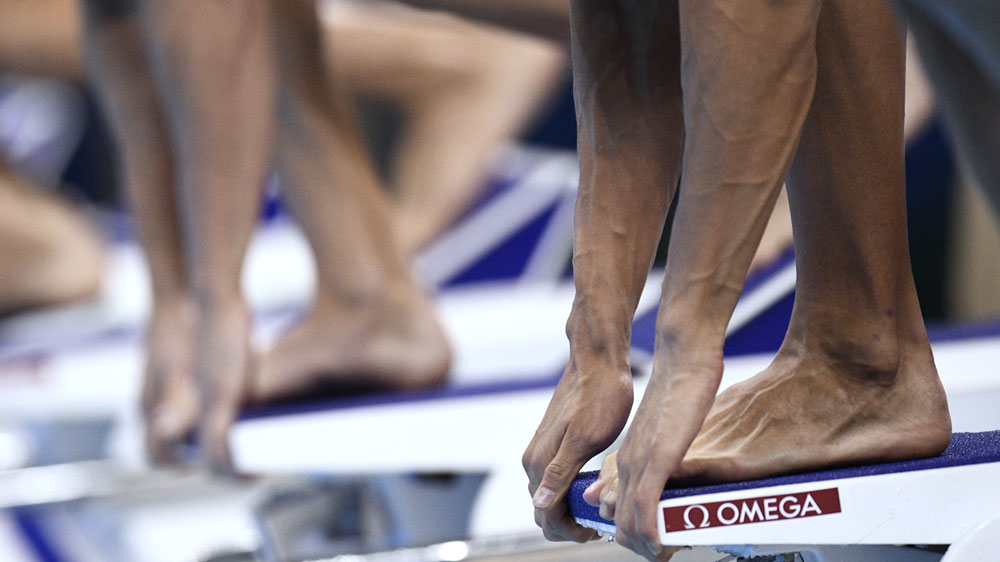 Swimmers line up on the blocks (AFP)