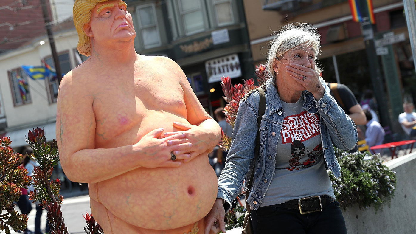 A woman stands beside a statue of a naked Republican presidential candidate Donald Trump, in New York's Union Square. The statue was removed by New York City Department of Parks & Recreation employees. (AAP)