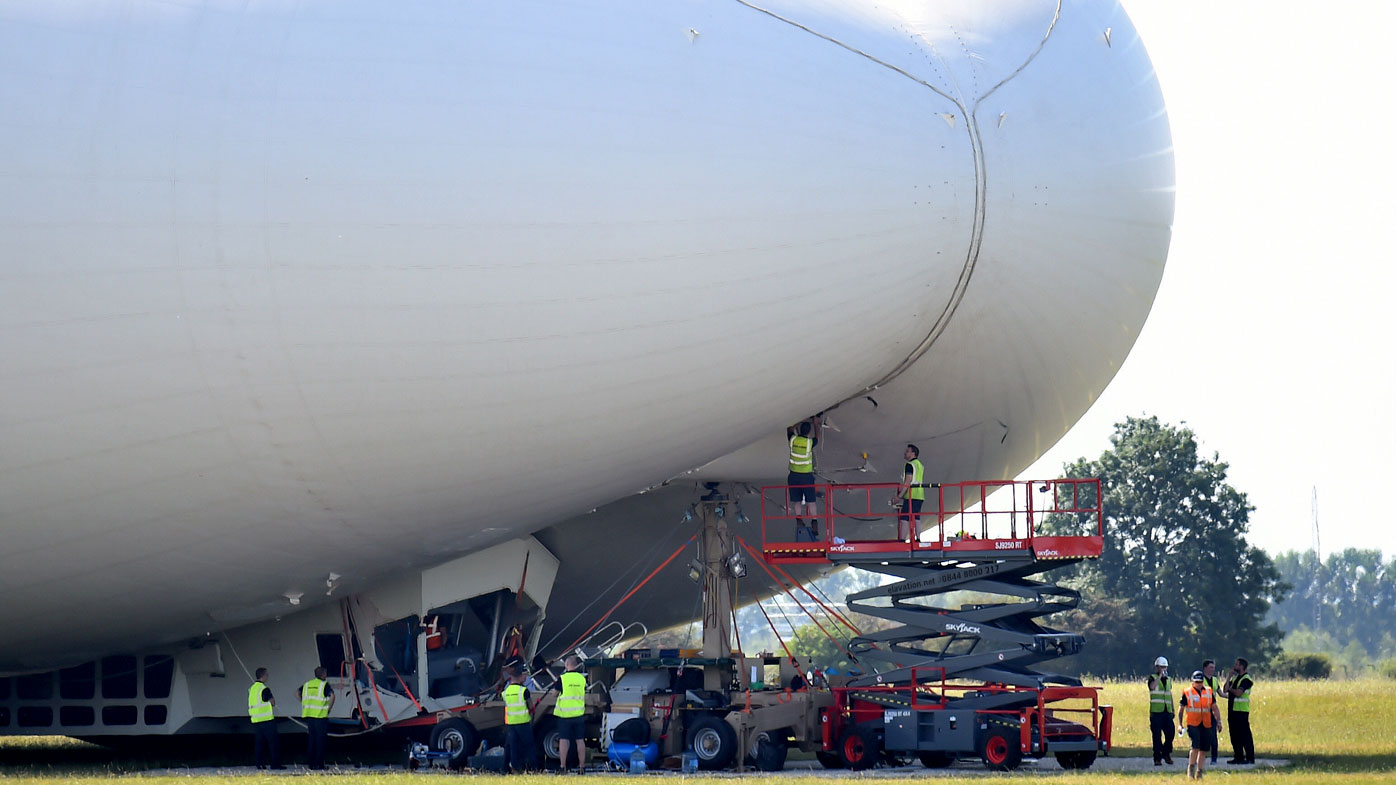 Crews assess the damage to the Airlander 10. (AAP)