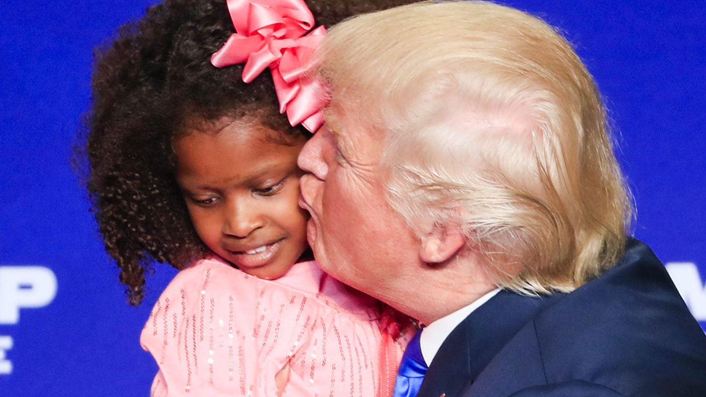 The child squirms as Trump plants a kiss on her. (AAP)