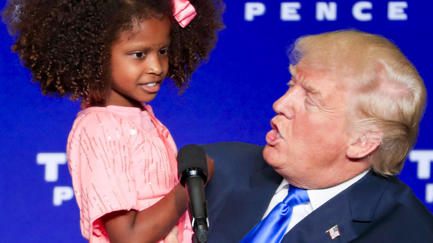 Trump and the girl at the rally. (AAP)