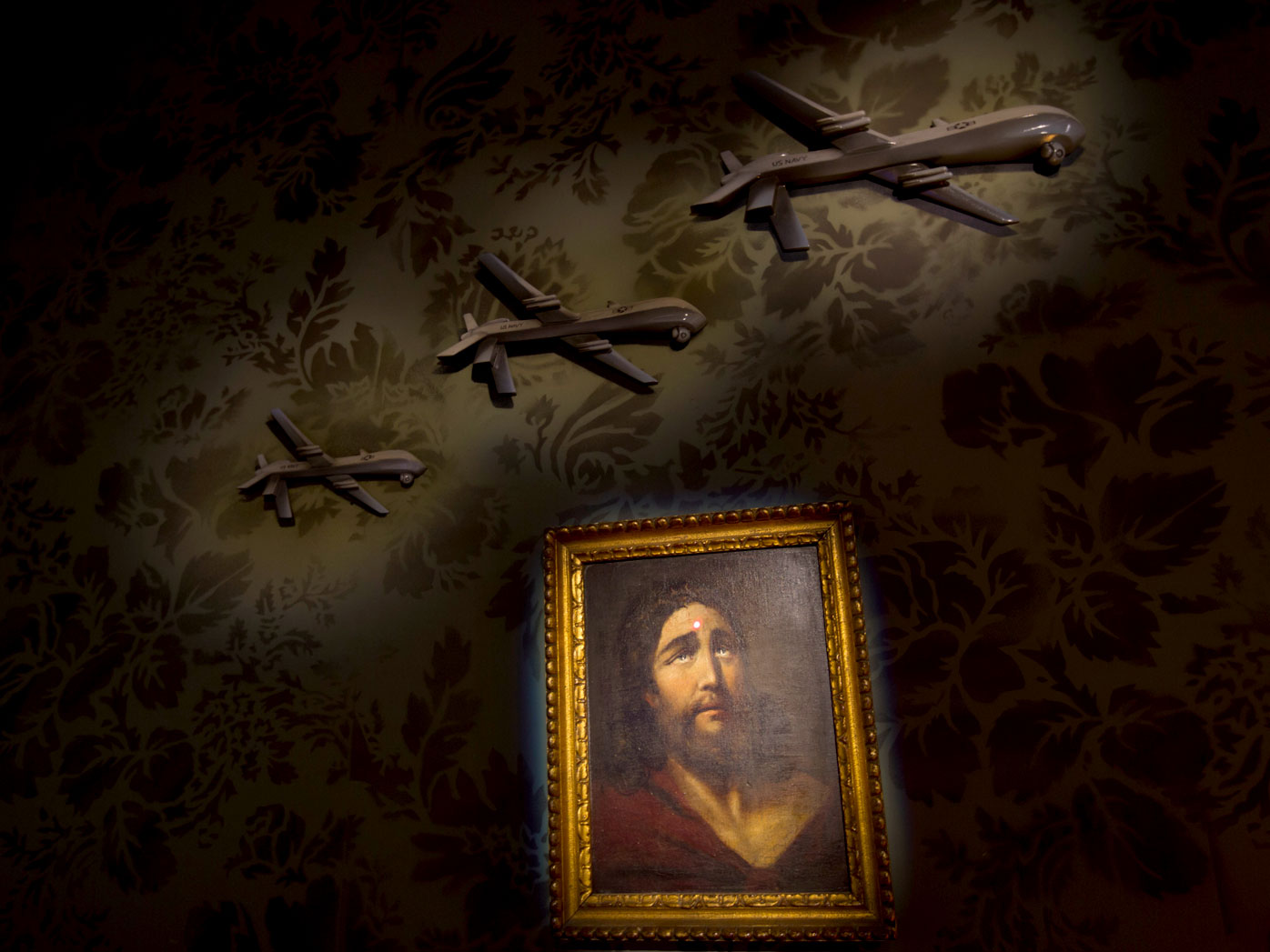 """A wall decorated with models of drones and a painting of Jesus with a sniper's dot on his forehead is seen in """"The Walled Off Hotel"""". (AAP)"""