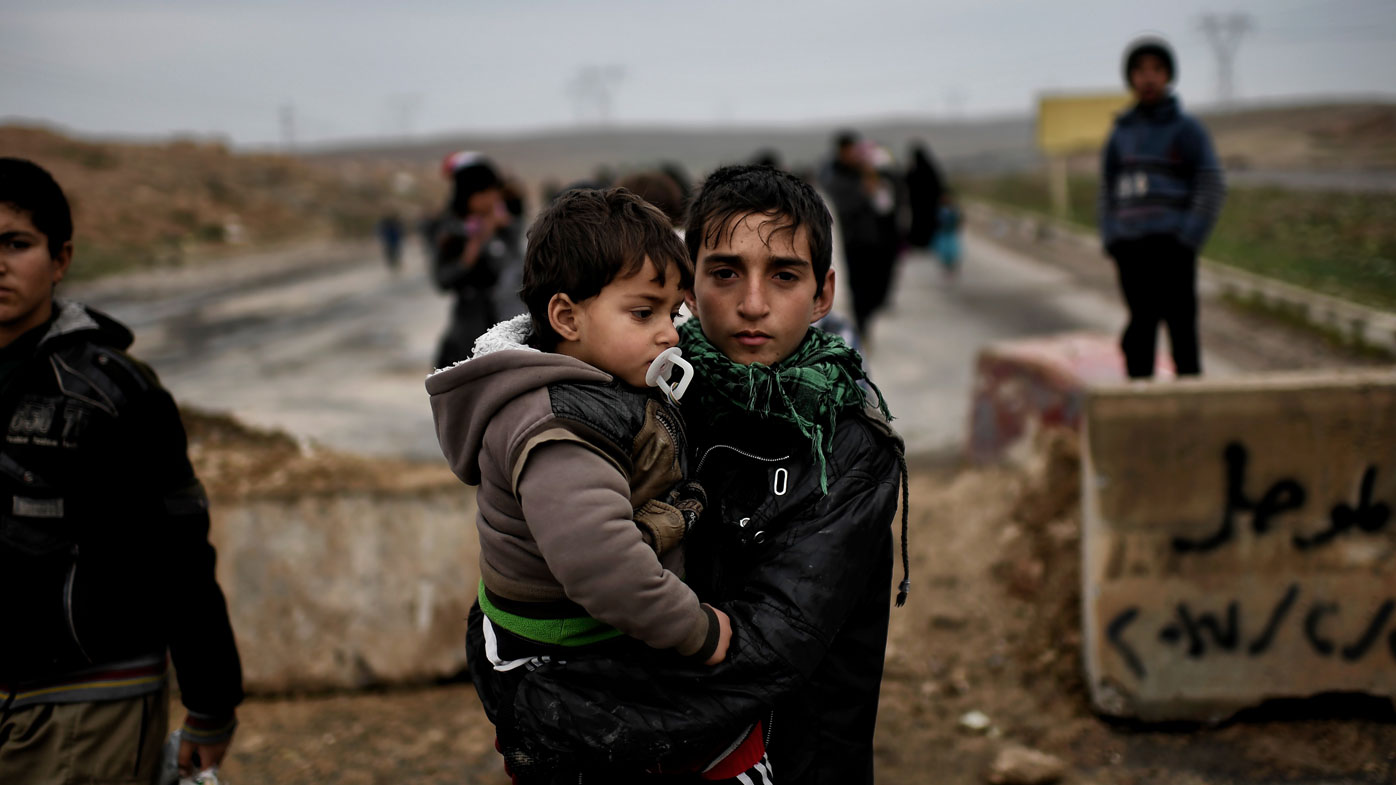 A boy holds a youngster as they walk to freedom in Mosul. (AFP)