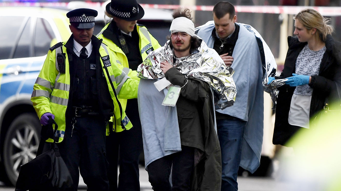An injured man is aided by police outside Westminster Palace in central London. (Getty)
