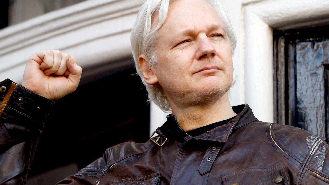 WikiLeaks editor Julian Assange appears on the balcony of the Ecuadorian embassy in London after Swedish authorities dropped their rape investigation. (AAP)