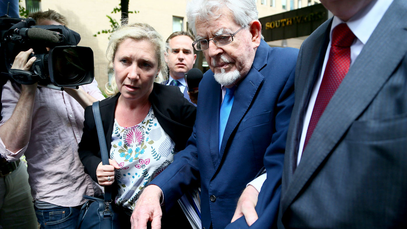 Rolf Harris is aided to a car as he leaves court. (AAP)