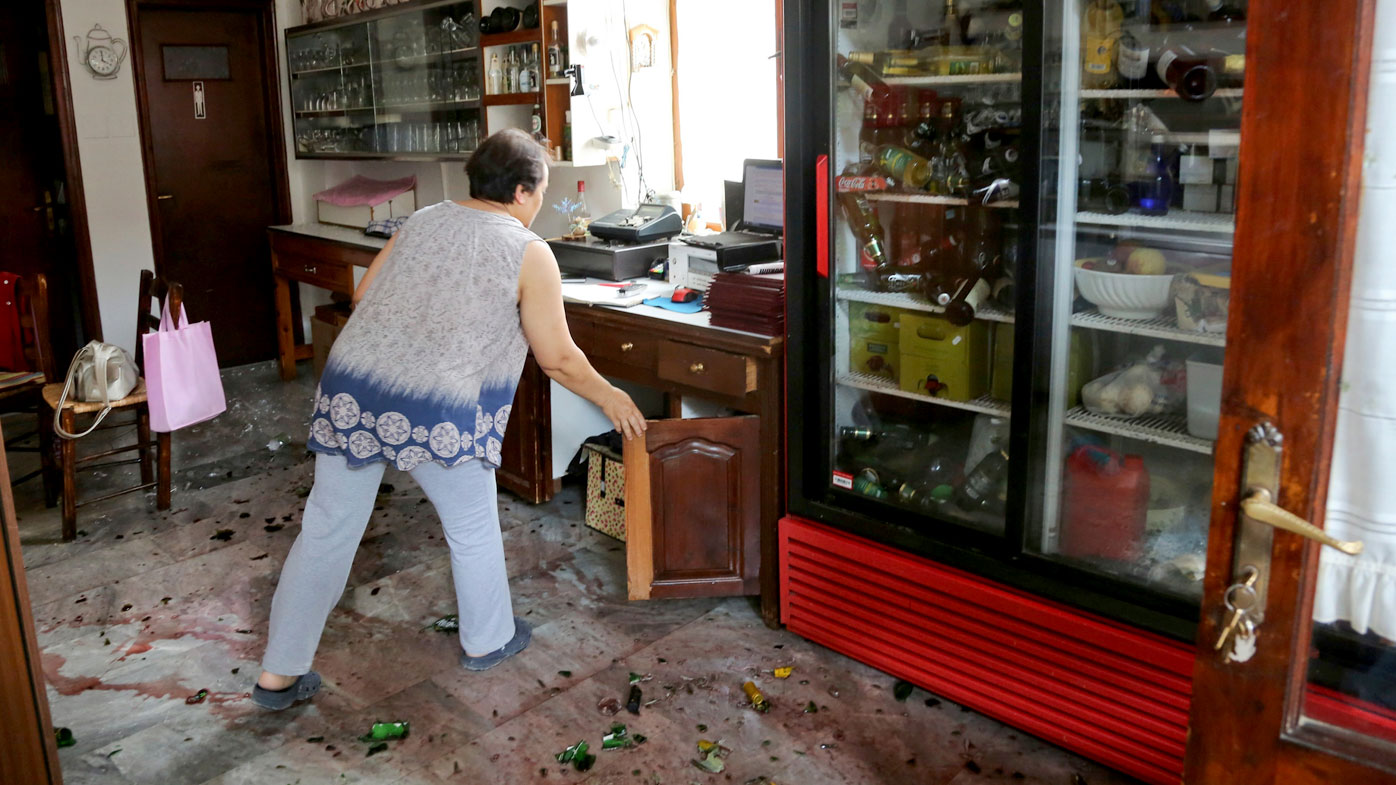 A woman clears her shop after an earthquake in the village of Plomari on the northeastern Greek island of Lesbos. (AAP)