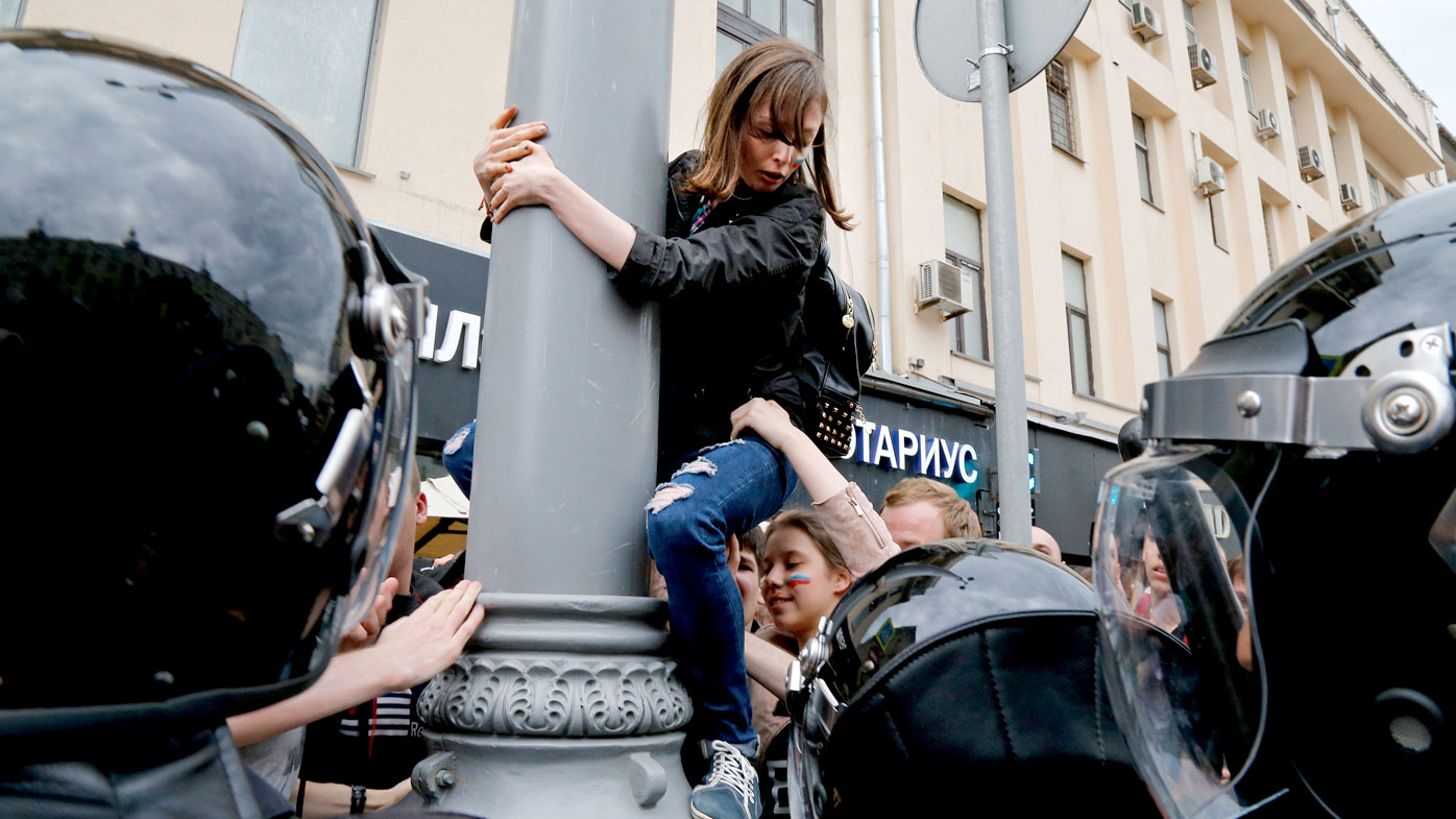 Police try to pull down a woman clinging to a post during a rally in downtown Moscow. (AAP)