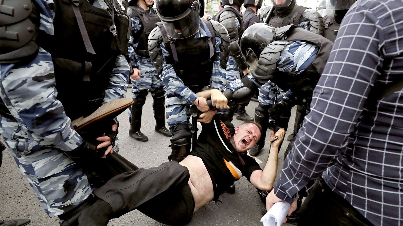 A man is carried away from a rally on Tverskaya street in central Moscow, Russia. (AAP)