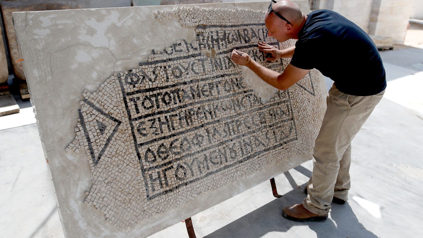 An archaeologist works on part of a 1,500-year-old mosaic floor bearing the names of Byzantine Emperor Justinian, at the Rockefeller Museum in Jerusalem. (AFP)