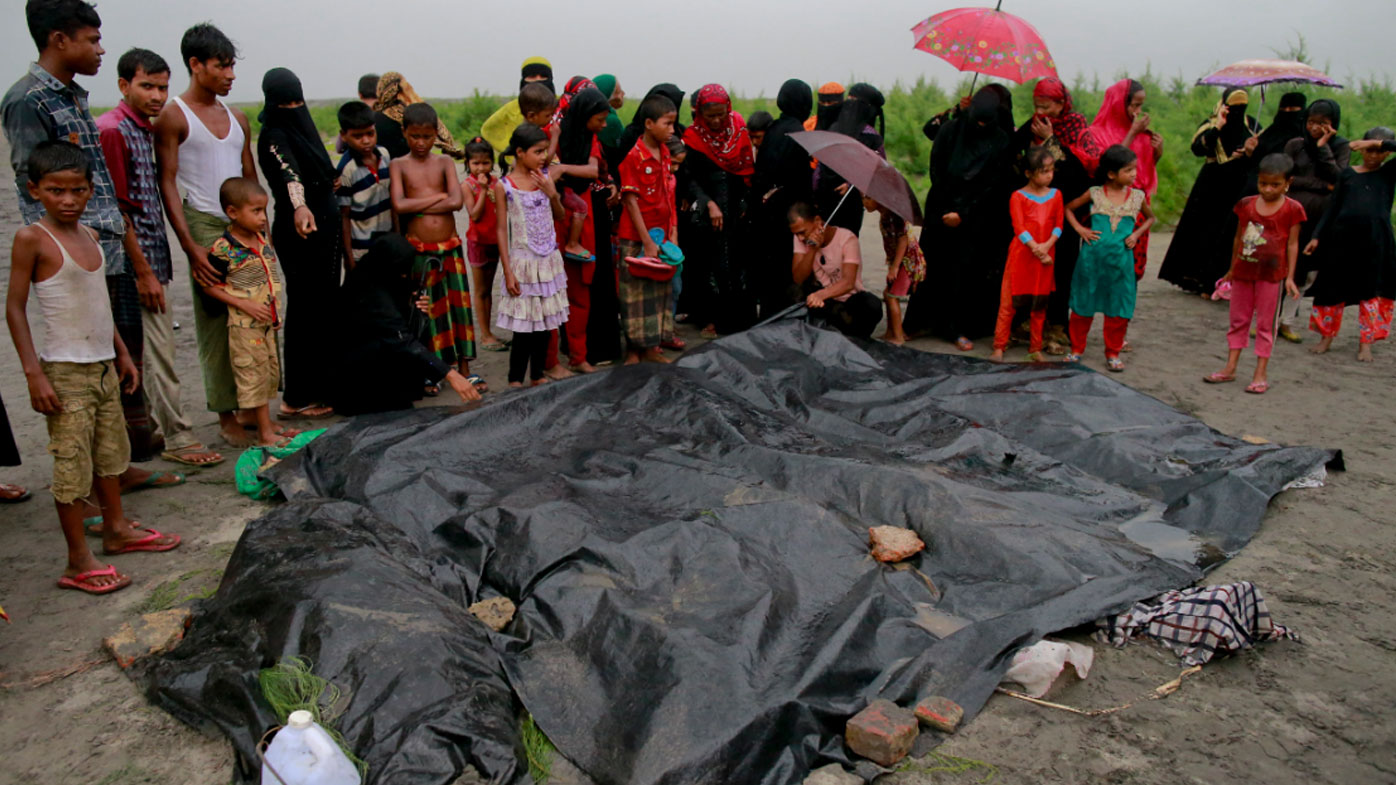 Bangladeshi villagers gather around bodies of Rohingya women and children after a boat capsized as they fled increasing violence in their home villages. (AAP)
