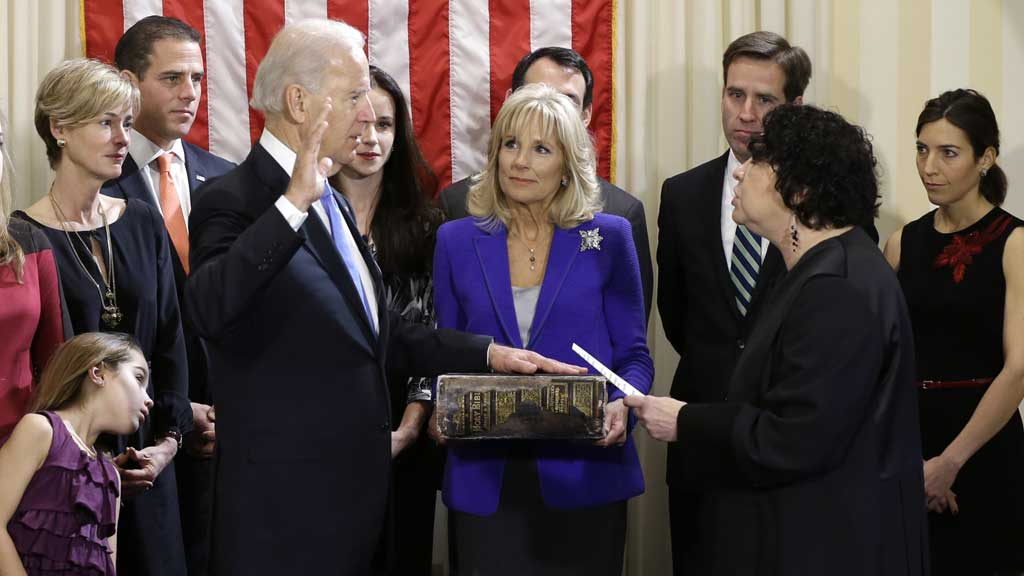 Joe Biden takes the oath of office alongside Kathleen and Hunter Biden, far left, and Beau and Hallie Biden, far right. (AAP)