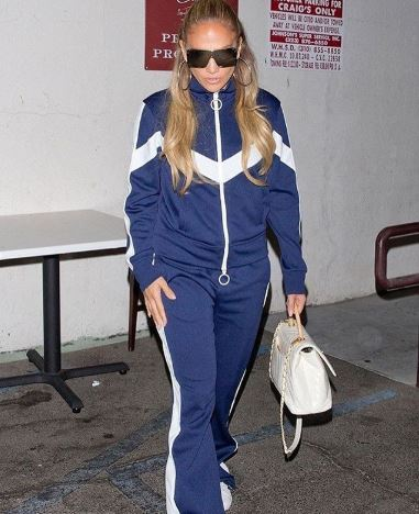 """<a href=""""https://style.nine.com.au/2018/08/22/13/25/jennifer-lopez-red-carpet-looks"""" target=""""_blank"""" title=""""Jennifer Lopez is better known for her bedazzling jewels and Versace gowns"""" draggable=""""false"""">Jennifer Lopez is better known for her bedazzling jewels and Versace gowns</a> that she is for sweats, but for a night out in Los Angeles the singer took to the streets in a tracksuit.<br /> <br /> Lopez oozed effortless cool in a navy blue and white tracksuit from Off-White, a pair of large reflector sunglasses and crisp white sneakers for a dinner date to LA hotspot, Craig's, with boyfriend Alex Rodriquez.<br /> <br /> In recent years, the Selena actress has stuck to glamorous gowns, thigh-high boots and designer duds for public appearances, but she has a long history with the tried-and-true tracksuit.<br /> <br /> She was one of the first to <a href=""""https://style.nine.com.au/2017/08/02/11/37/style_juicy-couture-returns"""" target=""""_blank"""" title=""""bring Juicy Couture """" draggable=""""false"""">bring Juicy Couture </a>to the forefront of the style set in baby pink shorts for her """"I'm Real ft. Ja Rule"""" music video back in 2001, and the look remained a staple in her wardrobe throughout the early aughts.<br /> <br /> Comfortable, cool and practical, investing in a head-to-toe tracksuit is the only way to up your athleisure game this season.<br /> <br /> Click through to see HoneyStyle's pick of must-have tracksuits.<br /> <br />"""