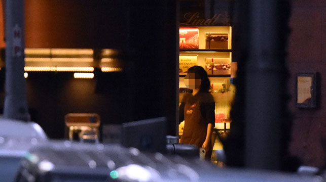 A hostage is seen going to the front door of the Lindt cafe to switch off the lights. (Getty)