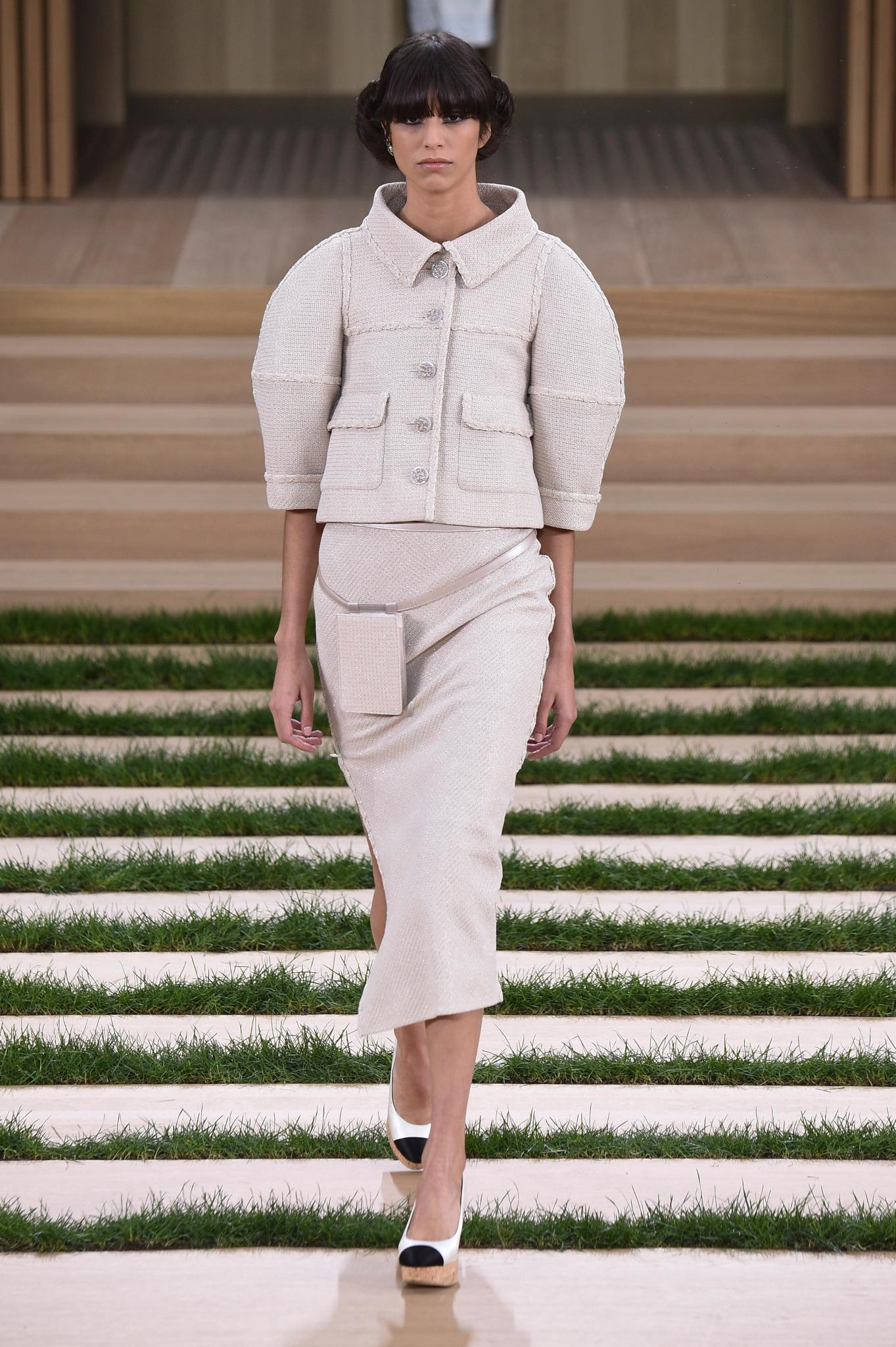 """<p>To showcase its haute couture collection, Chanel had models meander through an impeccably neat garden in chignons and two-tone platforms while wielding iPhone 6 cases that matched their outfit. </p><p>Sticking with a beige palette (""""Gabrielle Chanel was the Queen of beige,"""" said Karl Lagerfeld backstage), sleeveless evening dresses were accompanied by show-stealing rhinestone capes.</p><p>The collection marked the couture debut of models of the moment Gigi and Bella Hadid, who joined Chanel favourite Kendall Jenner on the runway.</p>"""