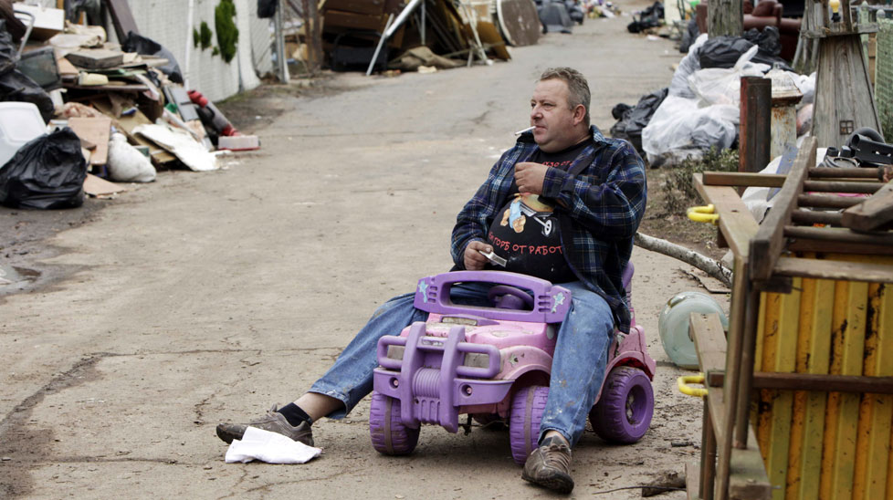 Volodymyr Krupa takes a cigarette break on his street while cleaning out his flood damaged home in the Staten Island. (AAP)
