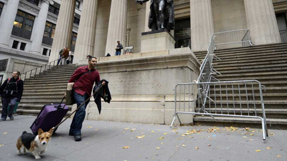 Kabir Bindra walks up Wall Street with his luggage and dog near the New York Stock Exchange.