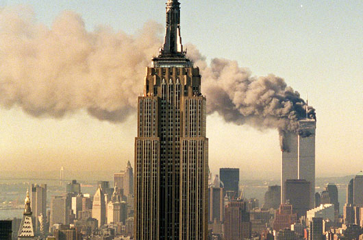 The twin towers of the World Trade Center burn behind the Empire State Building in New York. (AAP)