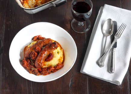 Sausages with roasted onion, tomato and polenta